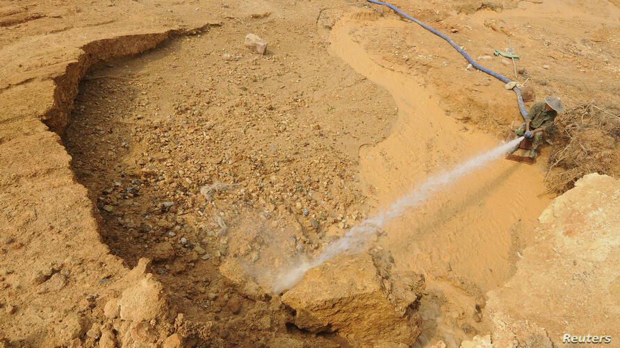 FILE - A laborer hoses water at the site of a rare earth metals mine at Nancheng county, Jiangxi province.