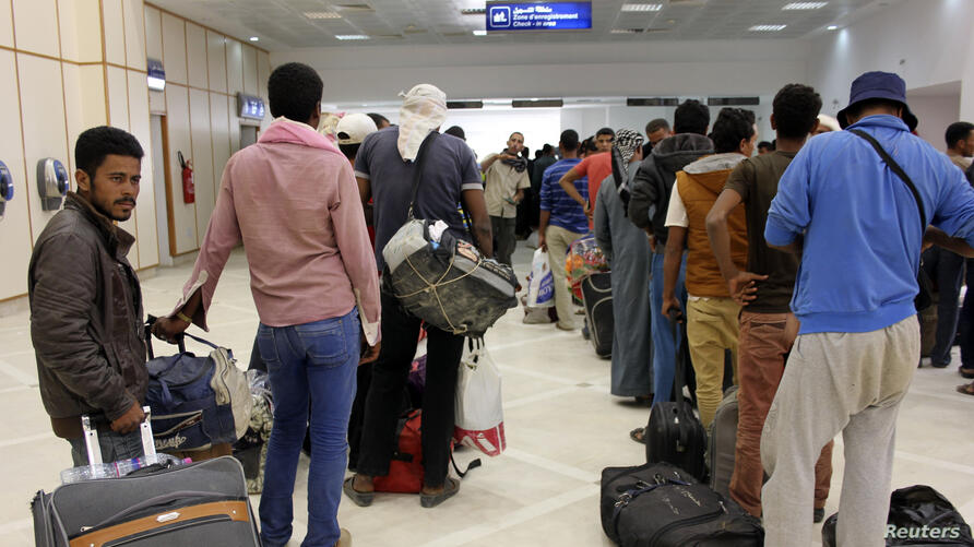FILE - Egyptian men wait to board their plane to return home, at the Gabes Matmata airport, south of Tunisia Aug. 6, 2014.