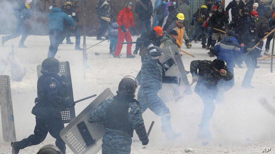 A police officer beats a protester during clashes in central Kyiv, Jan. 22, 2014.