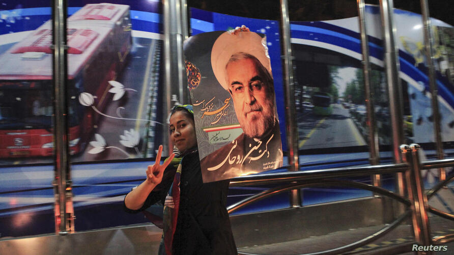 A supporter of moderate cleric Hassan Rohani celebrates his victory in Iran's presidential election along a street in Tehran, June 16, 2013.