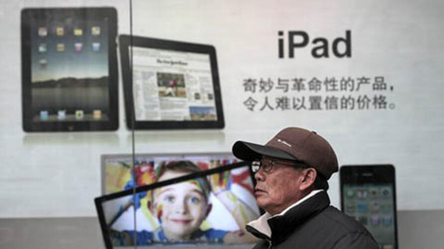 In this photo taken on Jan. 26, 2011 photo, a man stands near Apple's iPad advertisement in Shanghai, China. Apple Inc. said its audits found a doubling in labor, safety and other abuses by its suppliers in 2010, though it praised Taiwanese manufacturer F