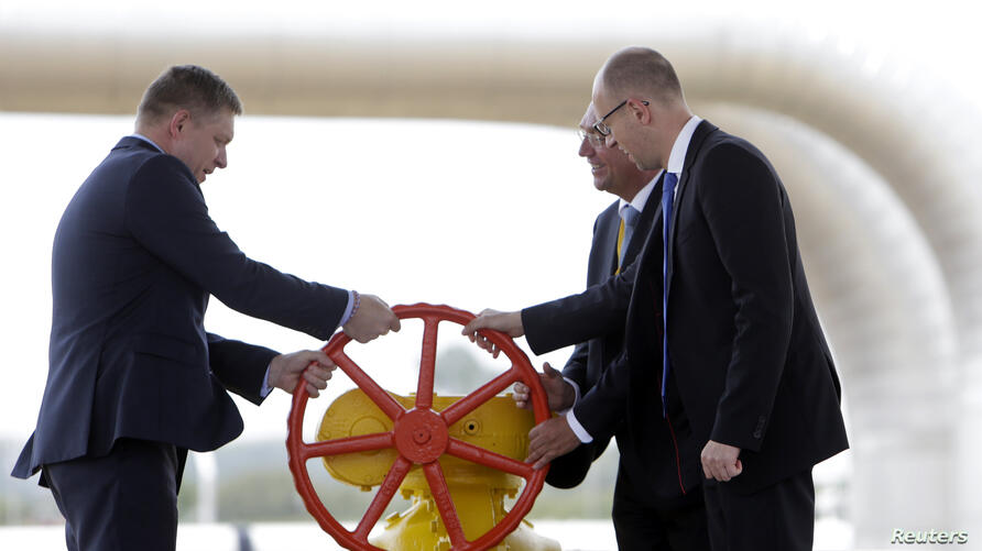 Slovakia's Prime Minister Robert Fico (L), Ukraine's Prime Minister Arseniy Yatsenyuk (R) and Director for Energy Markets at the European Commission Klaus-Dieter Borchardt open the Vojany-Uzhhorod pipeline during the official launch ceremony at a compress
