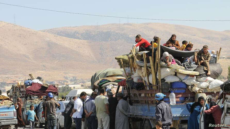 Syrian refugees, fleeing the recent fighting in Arsal, wait by trucks in Majdel Anjar in the Bekaa Valley, near the Lebanese border with Syria. The refugees, who had sought shelter in Arsal, were attempting to head back to Syria; however, they say auth...