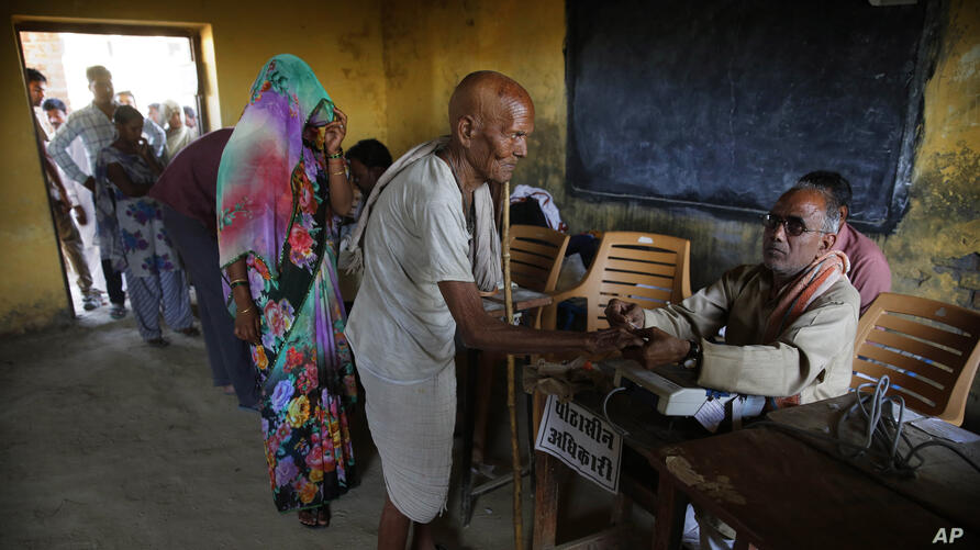 A polling official, right, marks the finger of an elderly man with indelible ink before he casts his vote at a polling station in Kunwarpur village, about 40 kilometers (25 miles) northwest of Jaunpur district, in the northern Indian state of Uttar Pra...