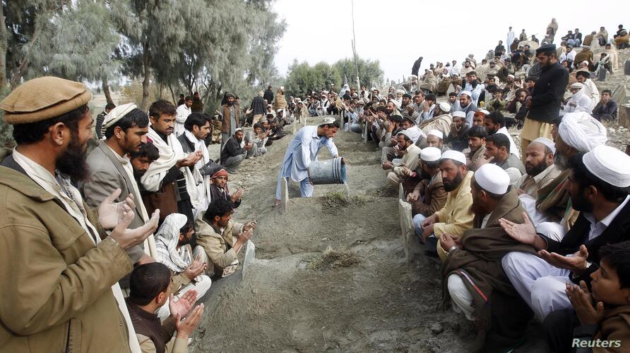 Villagers pray over the graves of girls who were killed by an explosion in Jalalabad, Afghanistan, December 17, 2012.