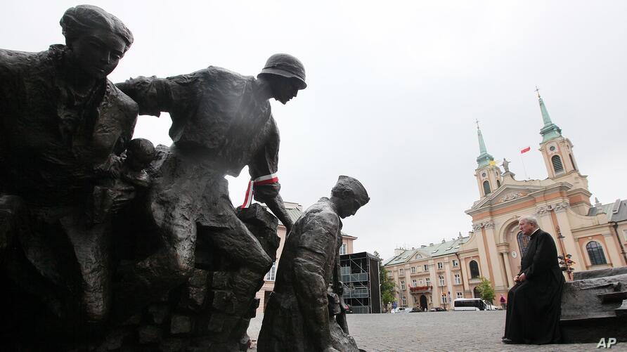 A Polish priest sits in front of the Warsaw Uprising monument in Warsaw. On the 70th anniversary of the uprising, Poland is honoring the fighters and victims of the rebellion against Nazi Germans by laying wreaths, sounding sirens and singing insurgent...