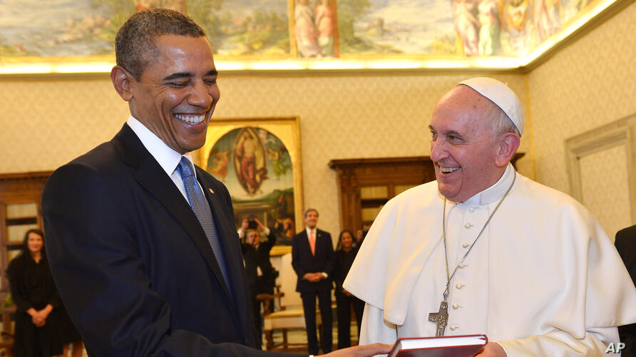 Pope Francis and U.S. President Barack Obama smile as they exchange gifts, at the Vatican.