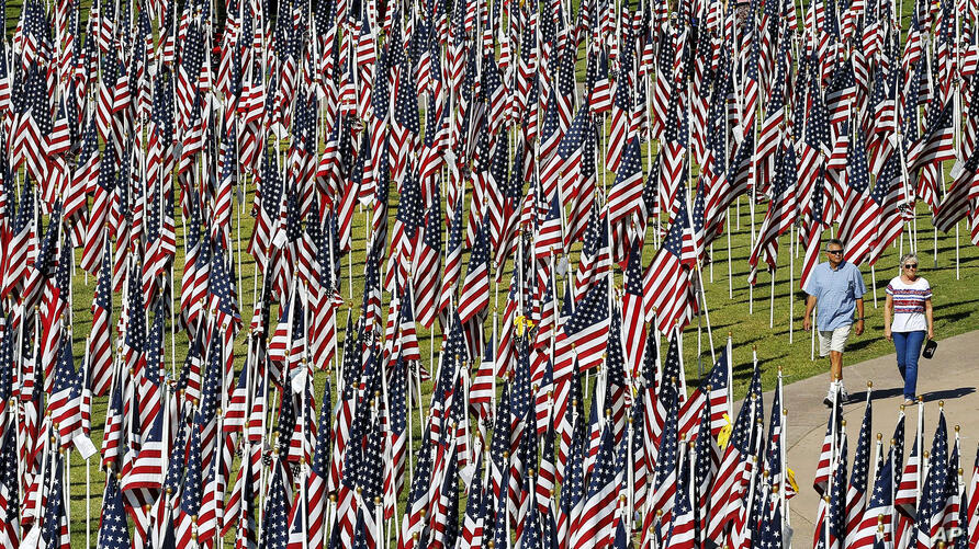 """A couple walks through the """"Healing Field"""" at Tempe Beach Park in Tempe, Arizona, USA, on the 12th anniversary of the 9/11 terrorist attacks. The display has nearly 3,000 flags with the names of those who died in the attacks."""