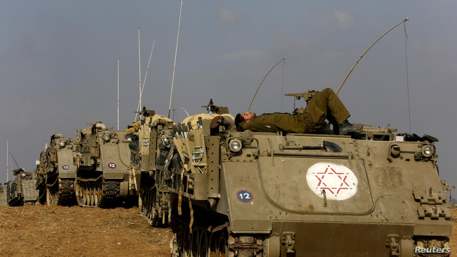 An Israeli reservist rests atop an armoured personnel carrier (APC) waiting to be transported off the Gaza border area November 22, 2012. A ceasefire between Israel and Gaza's Hamas rulers took hold on Thursday after eight days of conflict, although deep