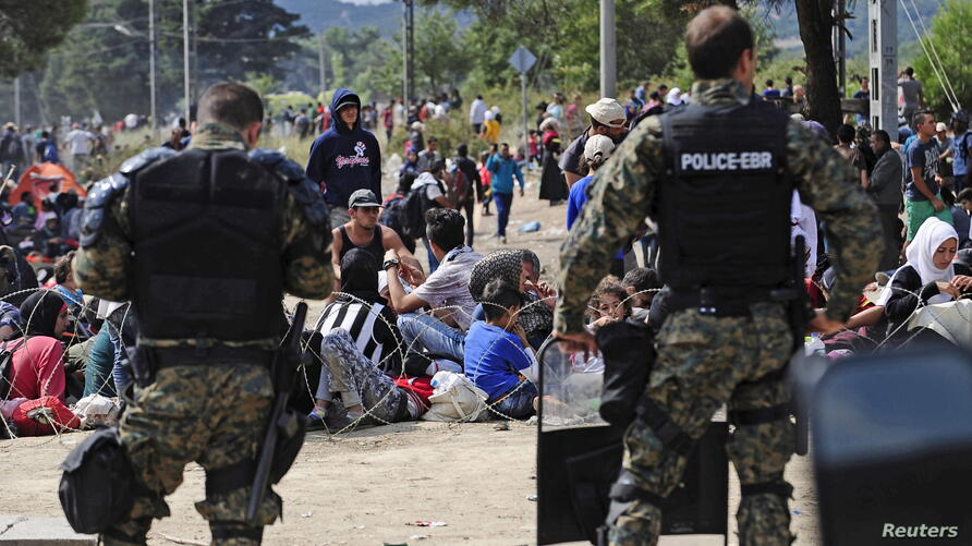 Macedonian special policemen guard the border as more than a thousand immigrants wait at the border between Macedonia and Greece, Aug. 21, 2015.