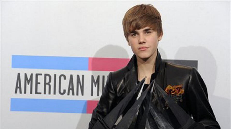 Justin Bieber hold his awards backstage at the 38th Annual American Music Awards on 21 Nov. 2010 in Los Angeles.