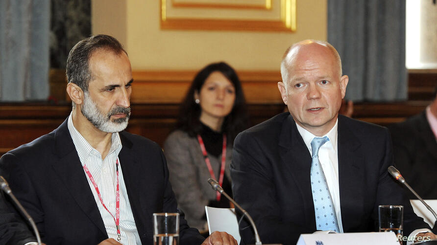 Britain's Foreign Secretary William Hague (R) and the leader of the Syrian opposition coalition Mouaz Alkhatib