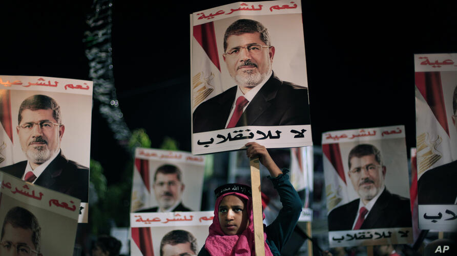 """Supporters of Egypt's ousted President Mohamed Morsi posters with Arabic writing which reads """"Yes for legality, No for the coup"""" during a protest outside Rabaah al-Adawiya mosque, Cairo, August 6, 2013."""