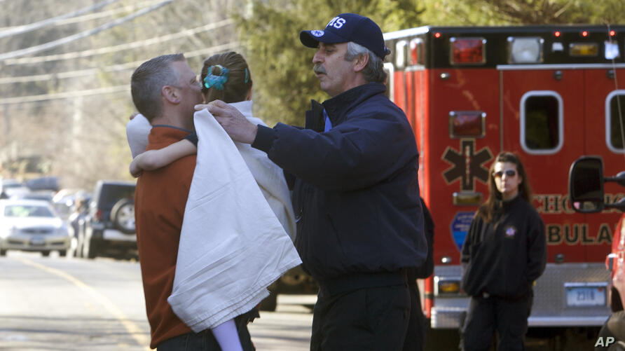 A young girl is given a blanket after being evacuated from Sandy Hook Elementary School following a shooting in Newtown, Connecticut, Dec.14, 2012.