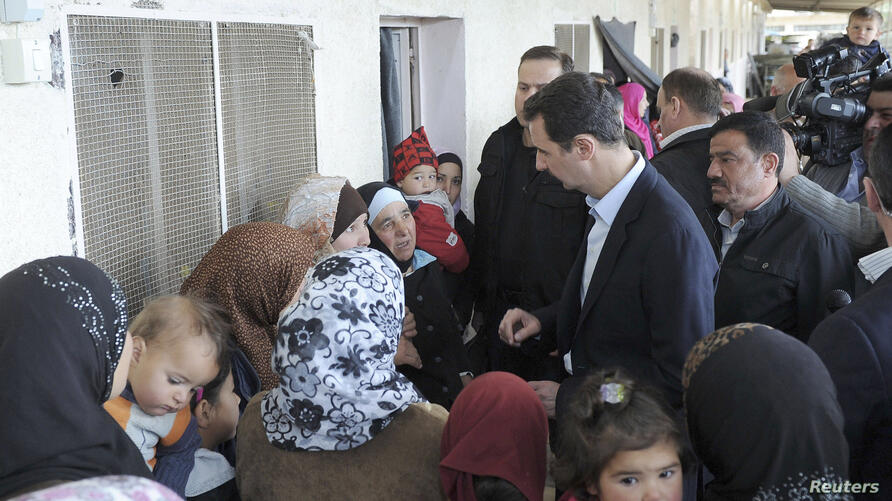Syria's President Bashar al-Assad (C) speaks with women during his visit to displaced Syrians in the town of Adra in the Damascus countryside March 12, 2014, in this handout photograph released by Syria's national news agency SANA. State television said A