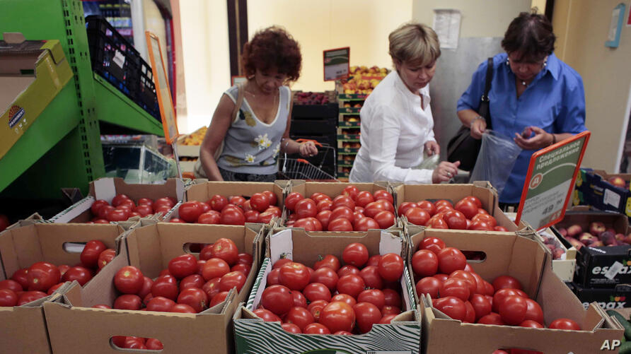 FILE - Women choose Dutch tomatoes at a supermarket in downtown Moscow. The Russian government has banned all imports of meat, fish, milk and milk products and fruit and vegetables from the United States, the European Union, Australia, Canada and Norway,