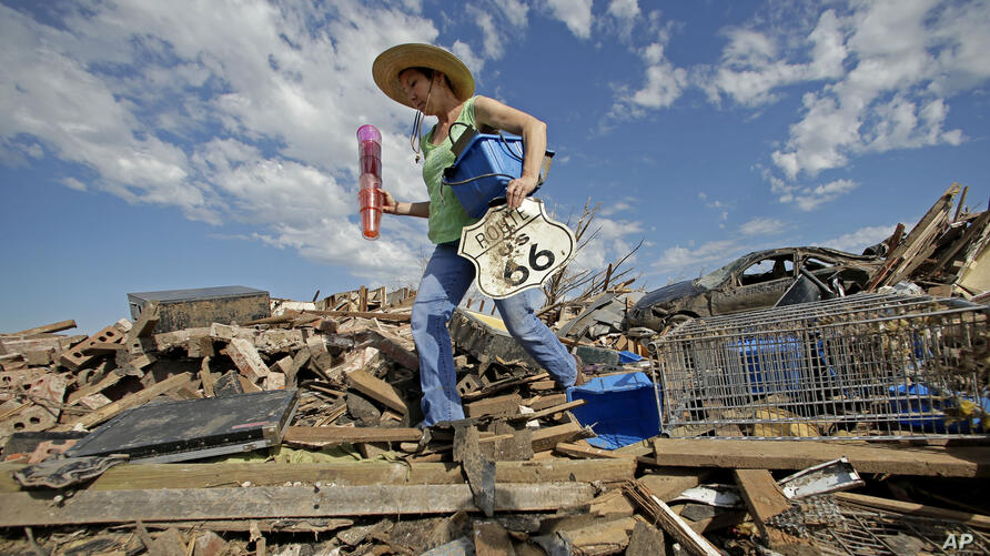 Susan Kates salvages items from a friend's tornado-ravaged home, May 22, 2013, in Moore, Oklahoma.