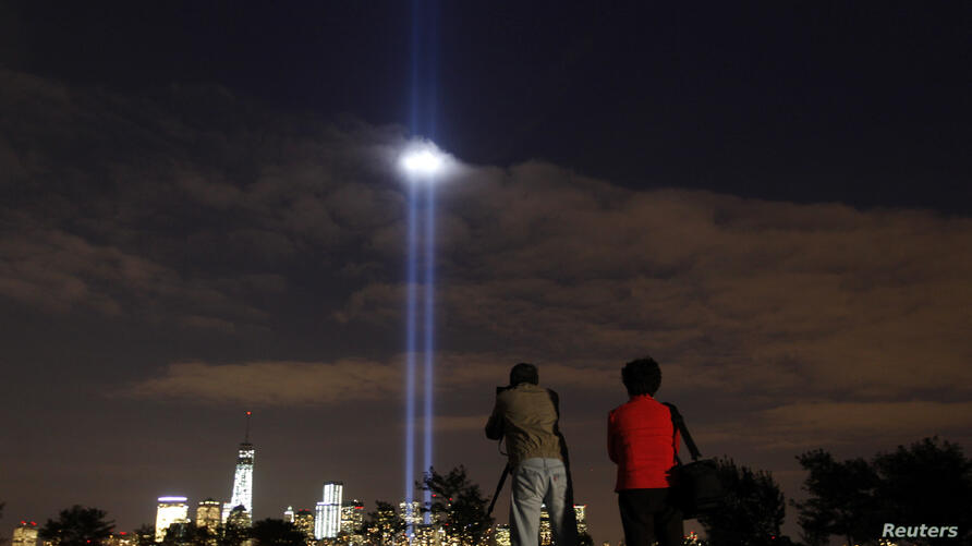 The annual Tribute in Light is tested in New York's Lower Manhattan as a man takes a picture at Liberty State Park in Jersey City, New Jersey, Sept. 9, 2013.
