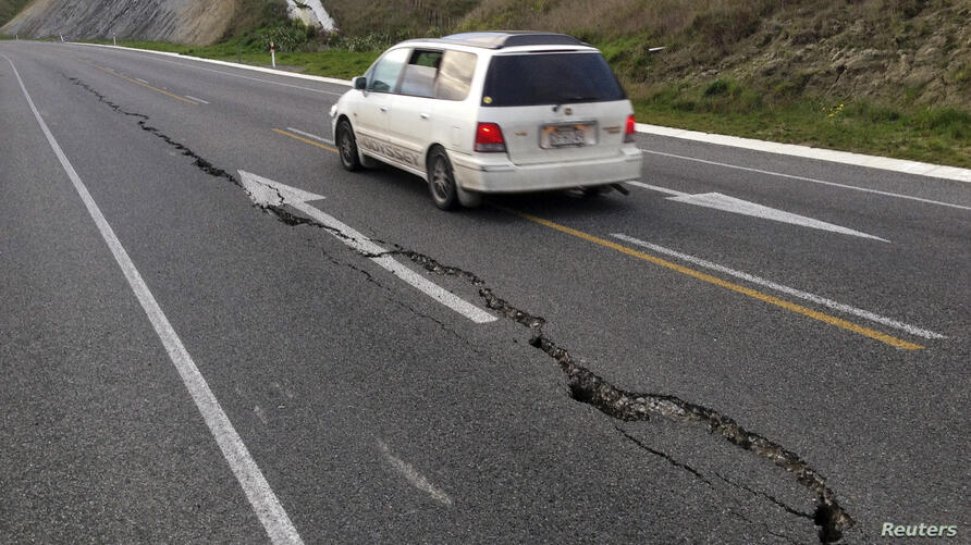A car drives past a crack in a road after an earthquake on the outskirts of the town of Seddon in the Marlborough region on New Zealand's South Island. A magnitude 6.5 earthquake struck south of New Zealand's capital, sending panicked Wellington worker...