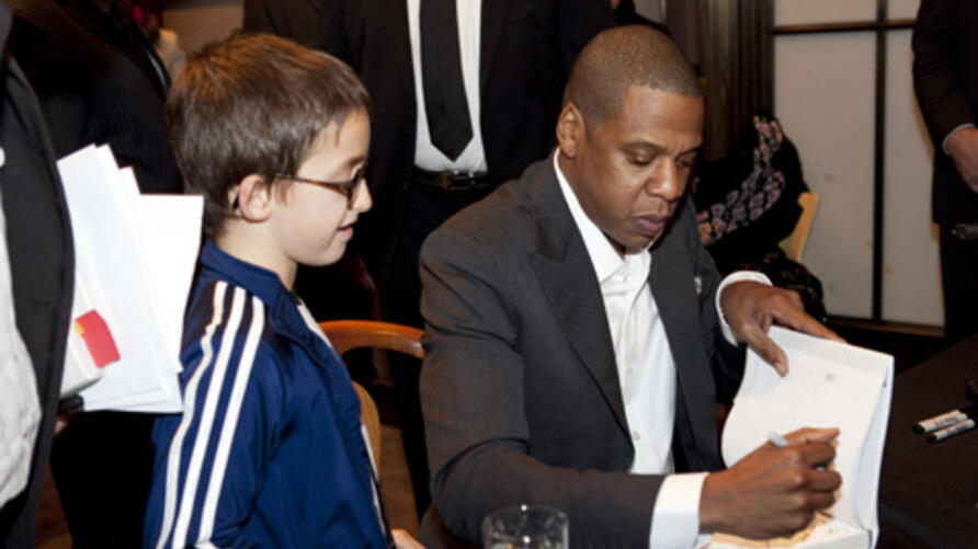 """Entrepreneur and rapper JAY-Z signs a copy of his book, """"Decoded,"""" for a young fan at the New York Public Library."""