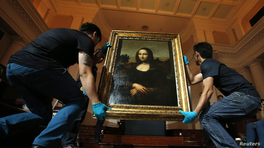"""Movers prepare to hang Leonardo da Vinci's """"Earlier Mona Lisa"""" painting ahead of its exhibition at The Arts House in Singapore, Dec. 12, 2014."""