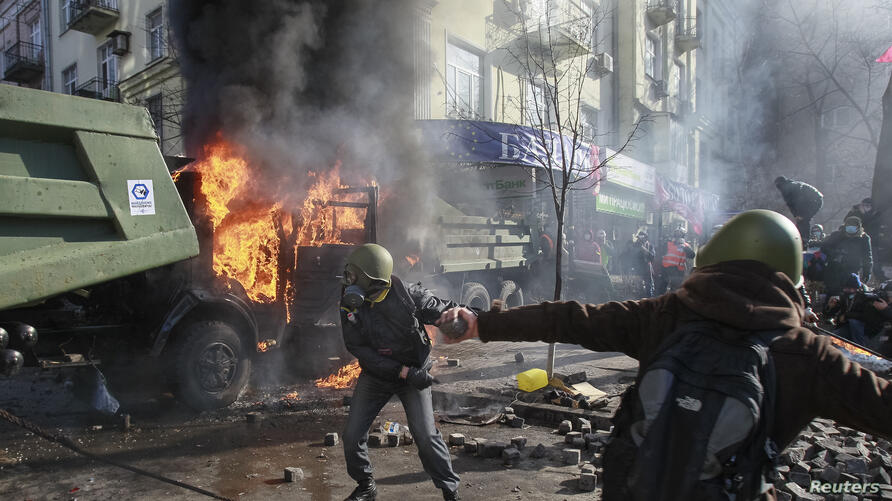 Anti-government protesters throw stones towards Interior Ministry officers during a rally, near Parliament, in Kyiv, Feb. 18, 2014.