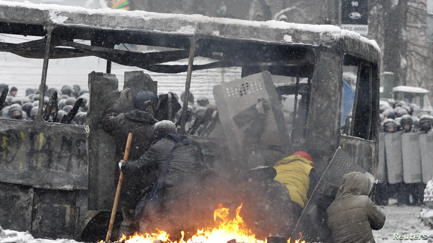 Pro-European protesters take cover behind a bus during clashes with riot police in Kyiv, Jan. 22, 2014.