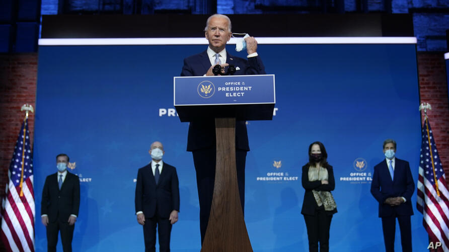 President-elect Joe Biden removes his face mask as he arrives to introduce his nominees and appointees to key national security…