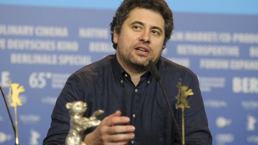 Radu Jude speaks next to his Silver Bear for Best Director for the film 'Aferim' at a news conference after the awards ceremony…