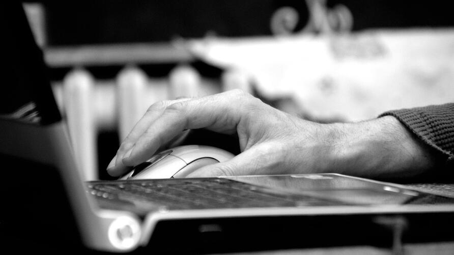 hand on mouse behind laptop