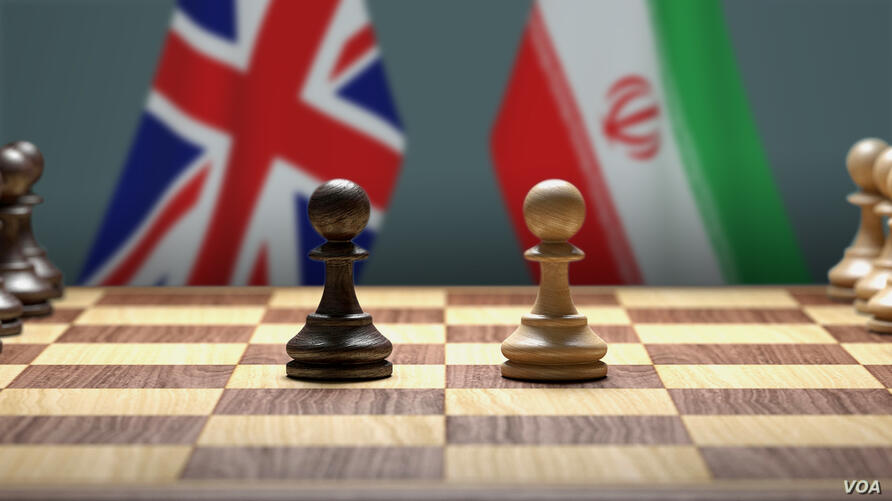 Flags of Great Britain and Iran behind pawns on a chessboard