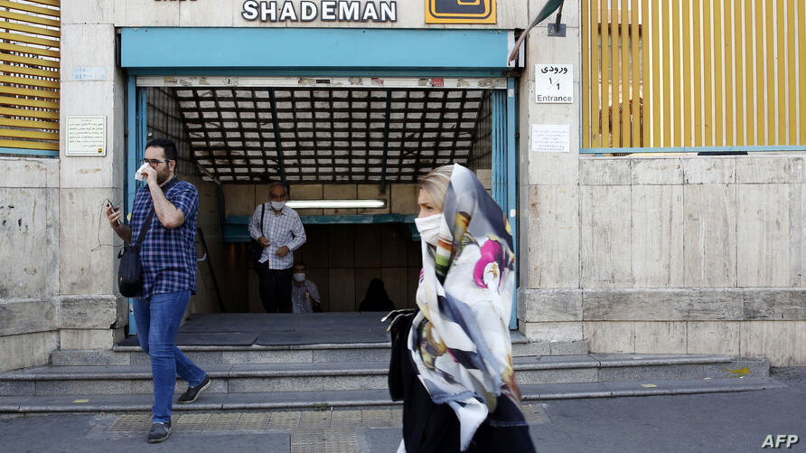 An Iranian woman wearing a face mask walks past a metro station in the capital Tehran on June 10, 2020 amid the coronavirus…