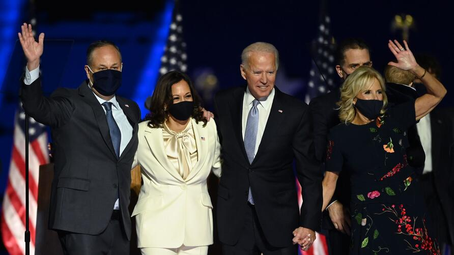 US President-elect Joe Biden and Vice President-elect Kamala Harris stand with spouses Jill Biden and Doug Emhoff after…