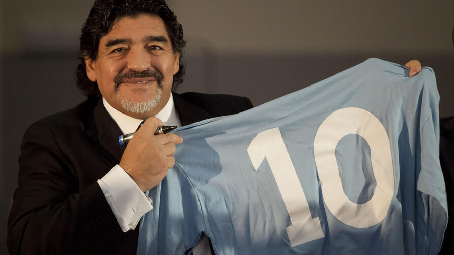 (FILES) In this file photo taken on February 26, 2013 Football legend Argentinian Diego Maradona holds a SSC Napoli number 10…