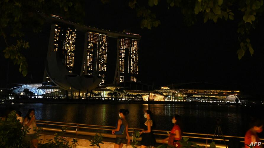 A general view of the Marina Bay Sands hotels and resorts is seen with the lights switched off for the Earth Hour environmental…