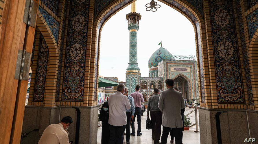 People walk in the courtyard of the Emamzadeh Saleh shrine in the Shemiran district of Iran's capital Tehran on April 14, 2021…