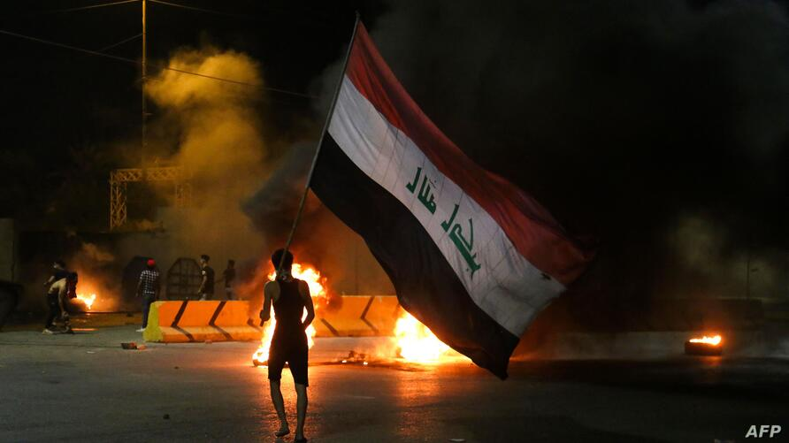 TOPSHOT - Iraqi protesters burn tyres in front of the Karbala governorate headquarters in the central  city of Karbala, early…