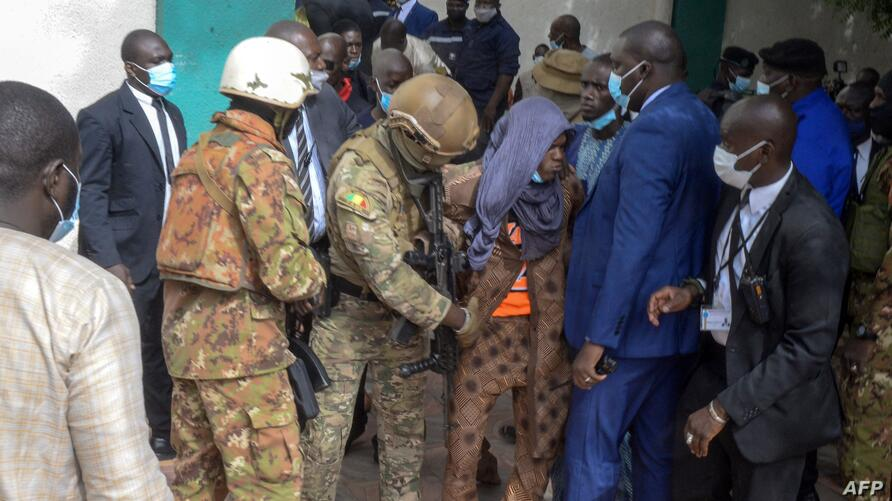 Security personnel escort an alleged attacker (C) from The Grand Fayçal Mosque in Bamako on July 20, 2021, after two assailants…