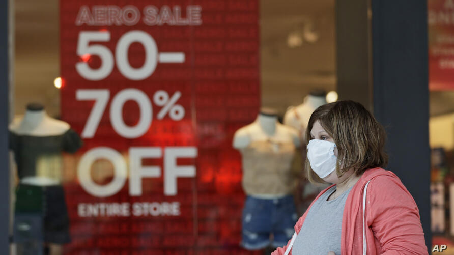A woman walks past a store with sale signs displayed at Great Lakes Mall, Wednesday, June 10, 2020, in Mentor, Ohio. Sales for…