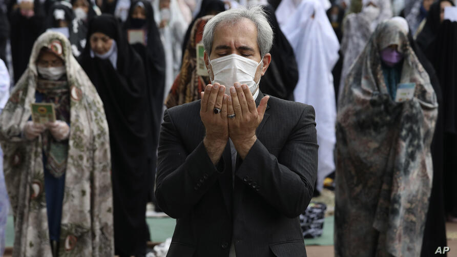 Worshippers wearing protective face masks offer Eid al-Fitr prayers outside a mosque to help prevent the spread of the…