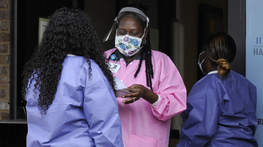 In this May 27, 2020, photo, health care workers talk outside a Lowndes County coronavirus testing site in Hayneville, Ala…