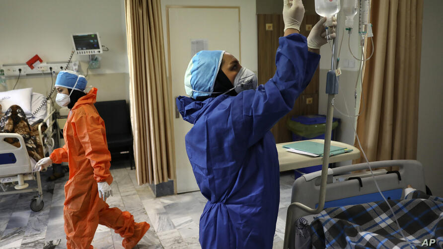 In this Tuesday, June 16, 2020, photo, nurses tend to COVID-19 patients at the Shohadaye Tajrish Hospital in Tehran, Iran…