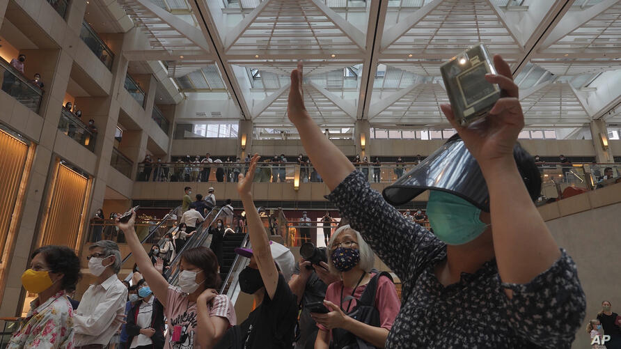 """Protesters gesture with five fingers, signifying the """"Five demands - not one less"""" in a shopping mall during a protest against…"""