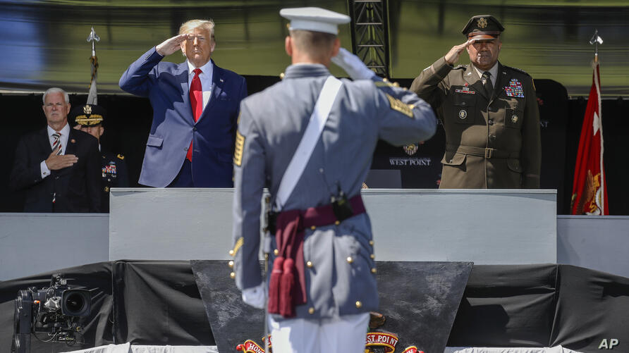 President Donald Trump, left, and United States Military Academy superintendent Darryl A. Williams, right, salute alongside…