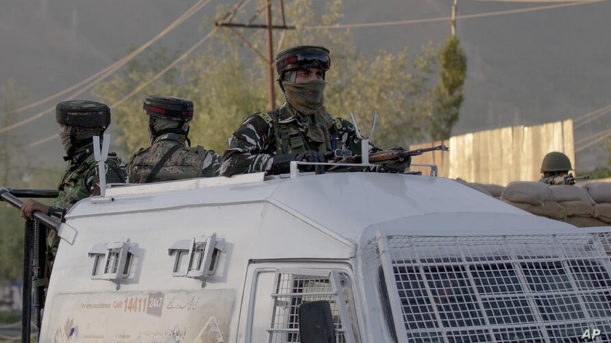 Indian paramilitary soldiers stand guard inside their armored vehicle near the site of a shootout on the outskirts of Srinagar,…