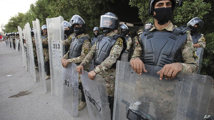 Riot police try to prevent protesters from storming the Iraqi Parliament Representation Building during anti-government…