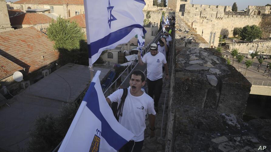 Israelis wave national flags as they parade on the walls surrounding Jerusalem's Old City to mark Jerusalem Day, after Israel…