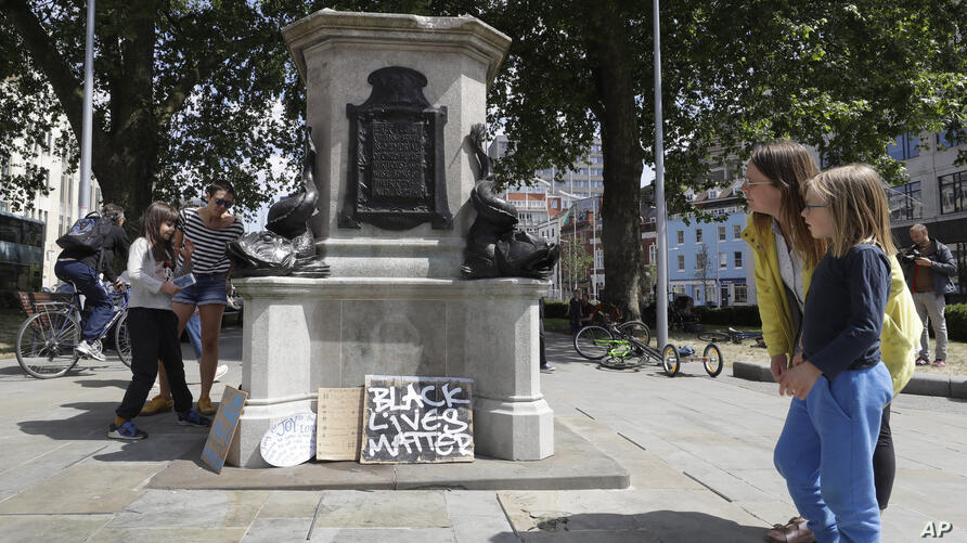 People look at the pedestal of the toppled statue of Edward Colston in Bristol, England, Monday, June 8, 2020, following the…