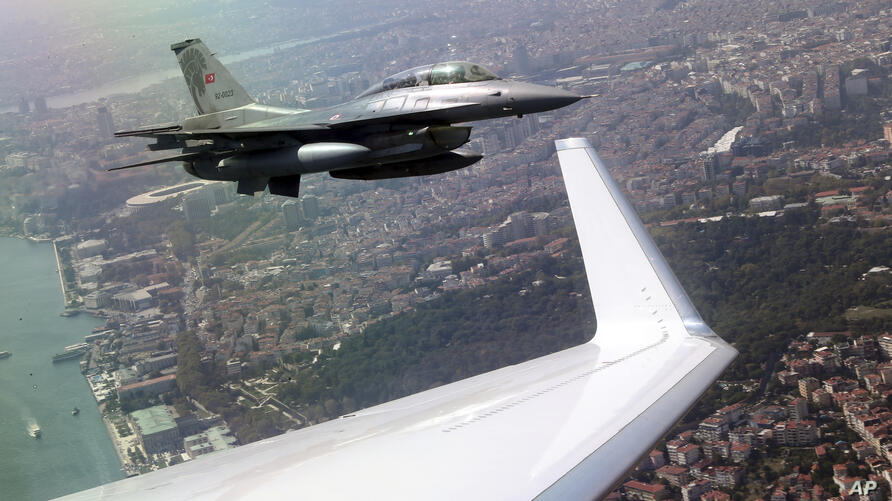 A Turkish army jet fighter escorts the plane of Turkey's President Recep Tayyip Erdogan as he arrives at the new airport in…