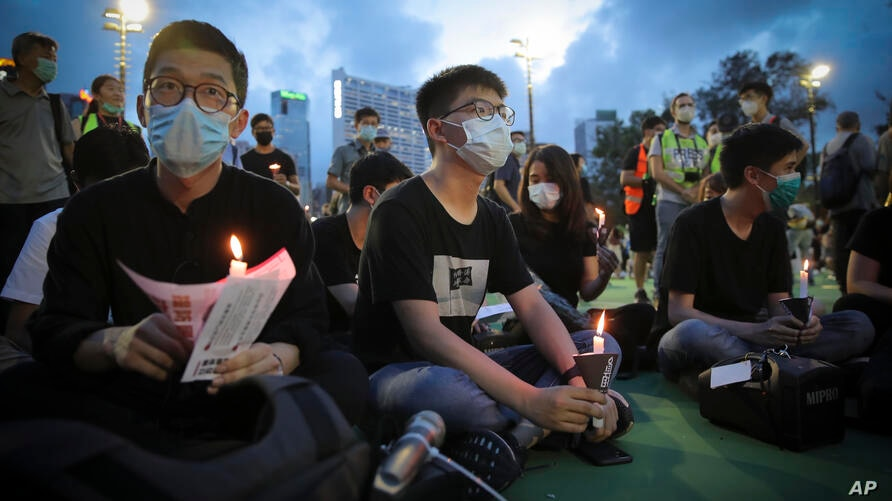 Hong Kong democracy activist Joshua Wong, center, holds a candle as he joins others for a vigil to remember the victims of the…